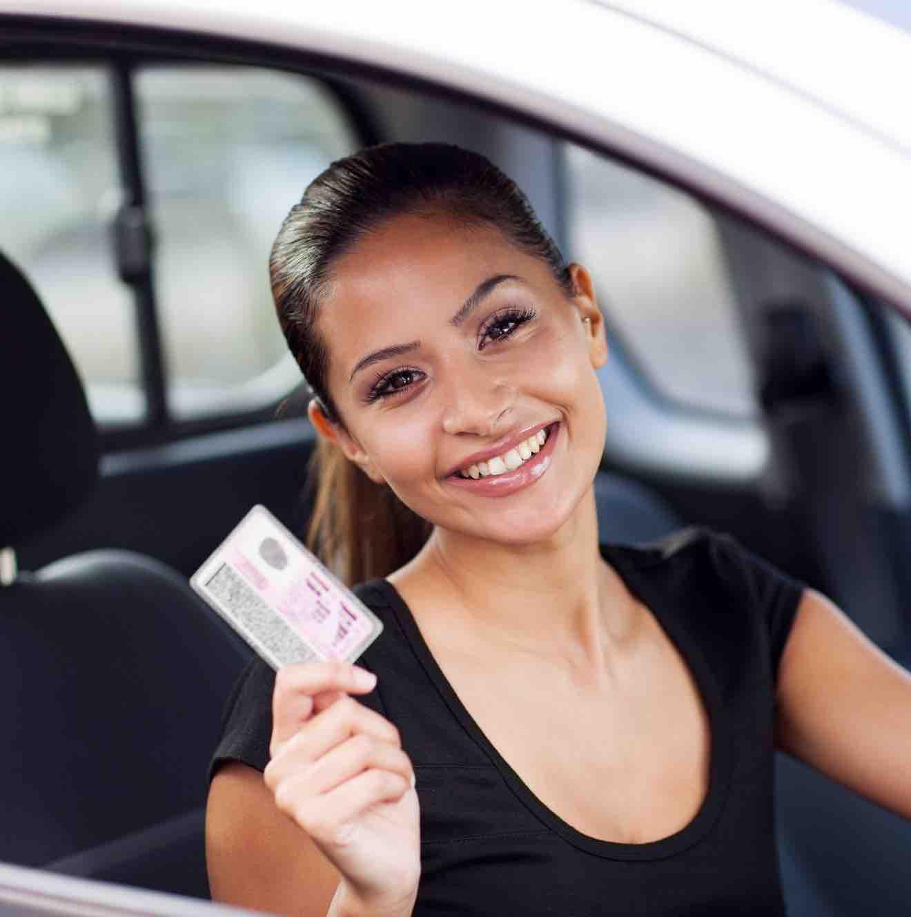 Frau sitzt am Steuer und hält Führerschein in der Hand