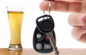 Bierglas Autoschlüssel, die von einer Hand gehalten werden