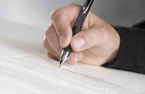 Mann hält Stift in der Hand und füllt Formular aus