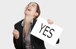 Frau hält Schild wo Yes drauf steht