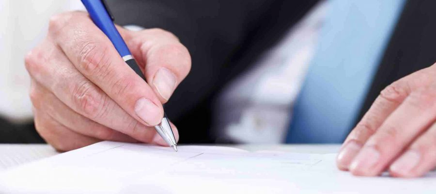 Man schreibt mit Kulli auf Papier